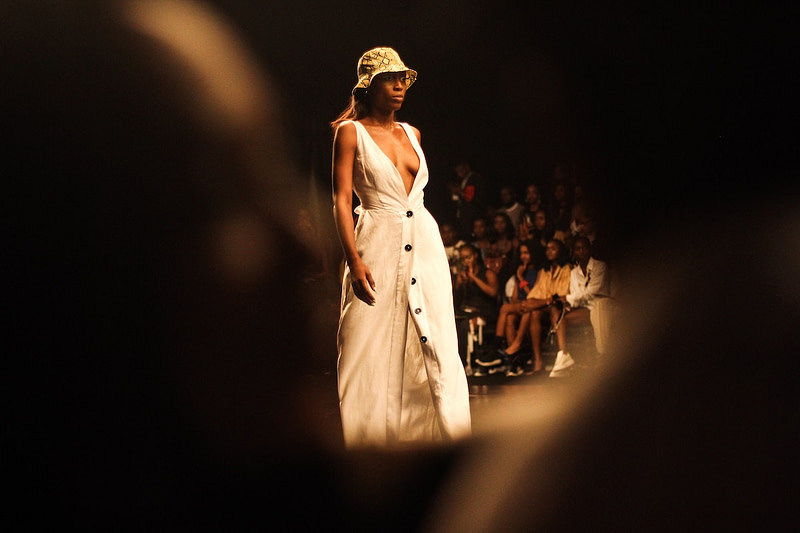 A model walking on a runway in article about fashion capitals.