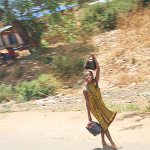 A girl walking along the road in rural Tanzania